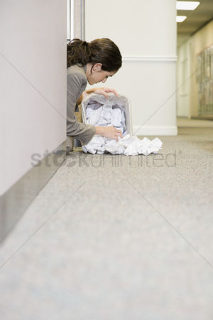 Interior : Woman searching in waste paper