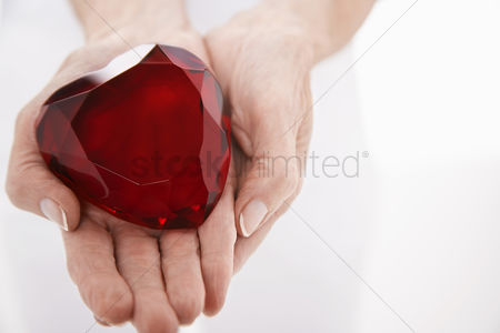 Body : Woman showing heart-shaped jewel close up on hands