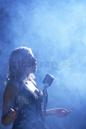 Arts : Woman singing at microphone in smoky place side view