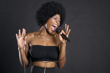 Curly hair : Woman singing on microphone over colored background