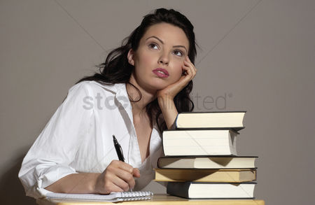 People : Woman sitting at her desk thinking of things to write