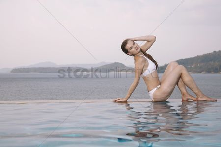 Arm raised : Woman sitting at the edge of pool