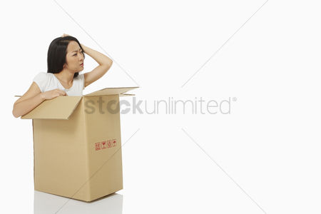 Frowning : Woman sitting inside of a cardboard box  looking confused