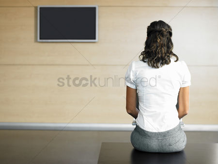 Instruction : Woman sitting on bench in lobby using laptop