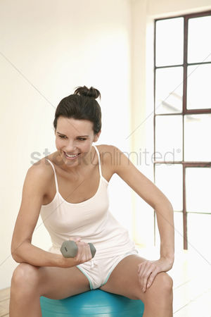 Dumbbell : Woman sitting on fitness ball