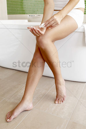 Body : Woman sitting on the bathtub holding a lotion
