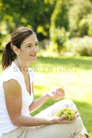 Green grapes : Woman sitting on the field eating green grapes