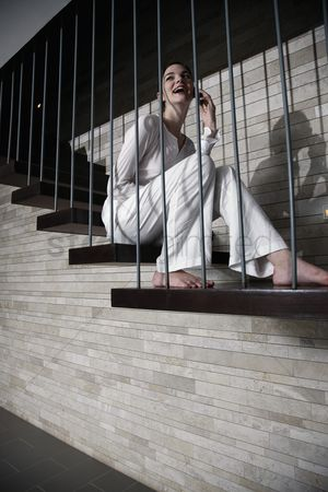 Staircase : Woman sitting on the stairs and talking on the phone