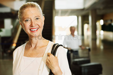 Pushing : Woman smiling with man pushing luggage cart in the background