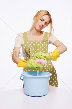 Housewife : Woman squeezing water from cleaning sponge