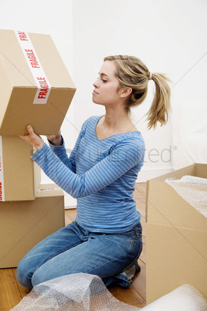 Denim : Woman stacking up sealed boxes
