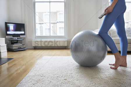 Flat : Woman standing at fitness ball watching television low section