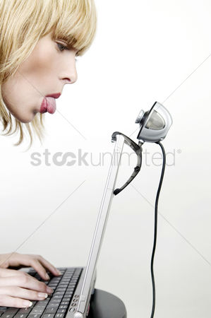 Modern lifestyle : Woman sticking out her tongue at a webcam while using laptop