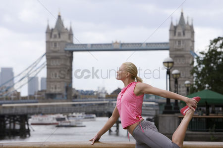England : Woman stretching in front of tower bridge england london