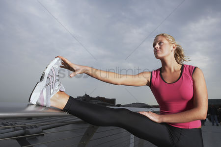 Fitness : Woman stretching on foot bridge low angle view