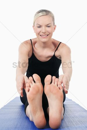 Practising yoga : Woman stretching on yoga mat