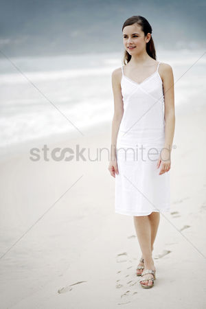 Contemplation : Woman taking a stroll along the beach