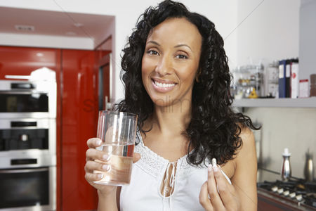 Medication : Woman taking medication smiling indoors portrait