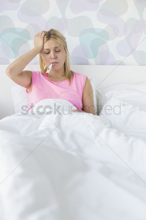 Thermometer : Woman taking temperature with thermometer while suffering from headache