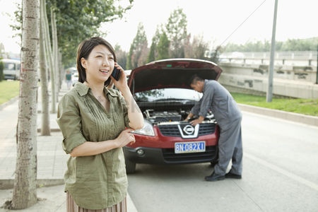 Fixing : Woman talking on phone while mechanic fixes her car