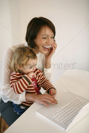 Enjoying : Woman talking on the phone and using laptop while taking care of her daughter