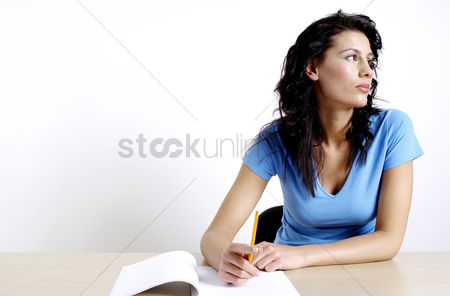 Educational : Woman thinking while writing