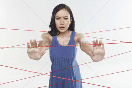Frowning : Woman trapped in between tangled wires