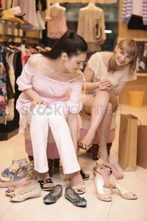 Choosing : Woman trying on shoes while her friend watches from the side
