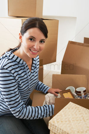 First : Woman unpacking moving box