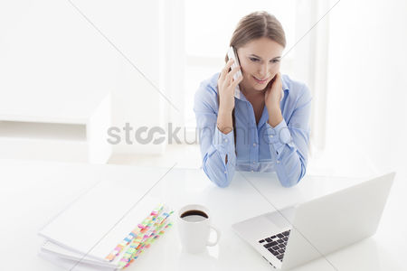Smiling : Woman using cell phone and looking at computer