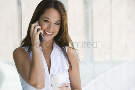 Cell phone : Woman using cell phone holding takeout coffee portrait
