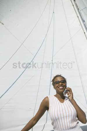 Gladness : Woman using cell phone on yacht
