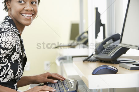 Interior : Woman using computer in office smiling