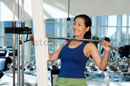 Club : Woman using exercise equipment in gymnasium