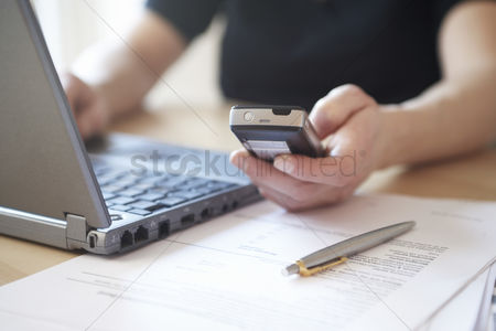 Mature : Woman using laptop and mobile phone close up