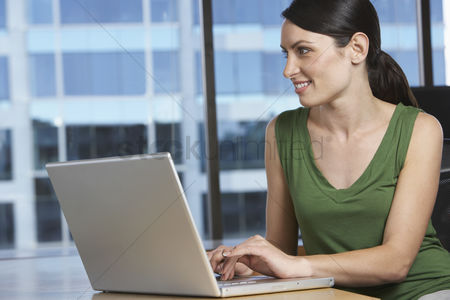 Desk : Woman using laptop at desk in office
