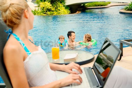Young boy : Woman using laptop looking at her family in the pool