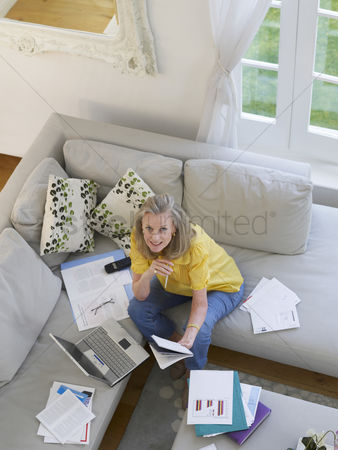 Sitting on lap : Woman using laptop sitting on sofa elevated view