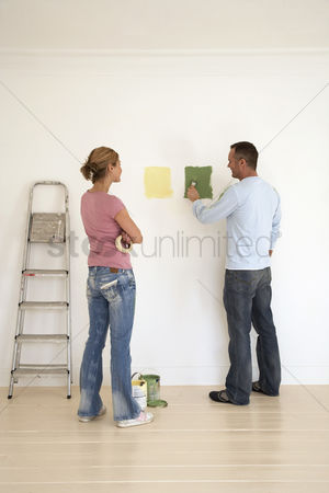 Paint brush : Woman watching man testing paint colours on wall