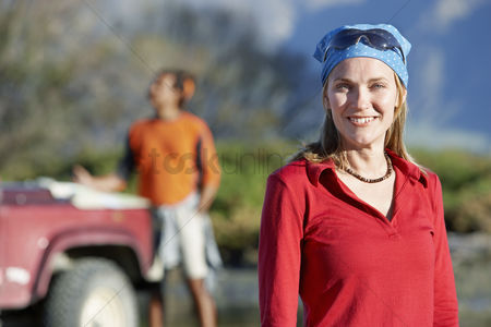 On the road : Woman wearing bandana with man by car behind outdoors focus on woman