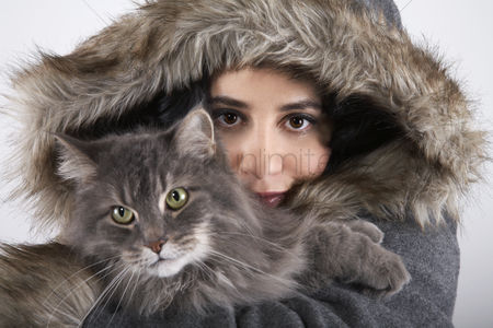 Animal head : Woman wearing hooded coat holding cat portrait close-up