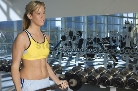 Posed : Woman weightlifting with barbell