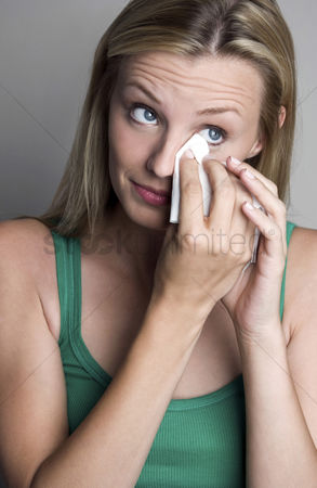 Loss : Woman wiping her tears with a tissue