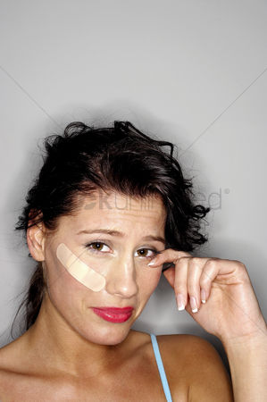 Sullen : Woman with a plaster on her face crying