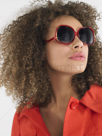 Curly hair : Woman with curly hair wearing sunglasses in studio