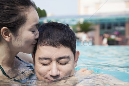 Kissing : Woman with eyes closed kissing man on the cheek in the water in the pool