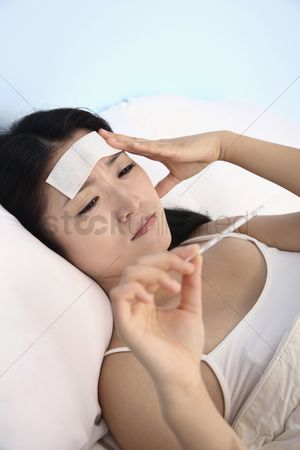 Thermometer : Woman with fever cool gel patch on forehead  checking thermometer