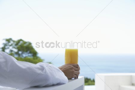 Body : Woman with glass of orange juice at the ocean