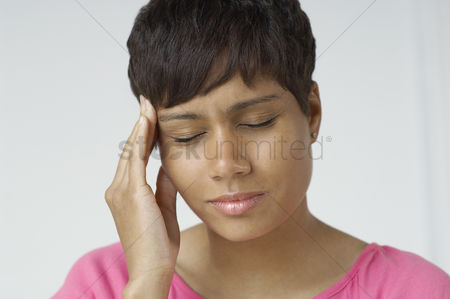 Pain : Woman with hand on forehead indoors
