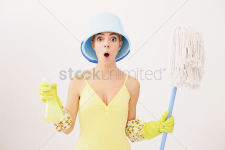 Housewife : Woman with pail on head holding mop and spray bottle